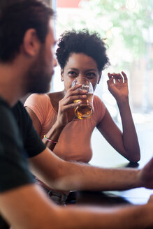 Woman drinking beer in a bar looking at boyfriend - LFEF00005