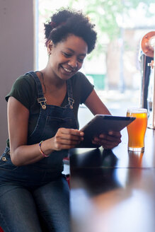 Smiling woman with beer glass using tablet in a bar - LFEF00011