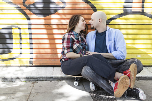Couple sitting on skateboard on city street - LFEF00020