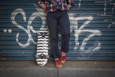 Low section of woman with skateboard at roller shutter - LFEF00023
