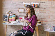 Smiling woman sitting on chair knitting - OCAF00024