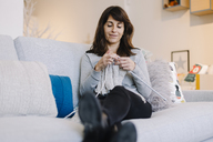 Woman sitting on couch knitting - OCAF00042