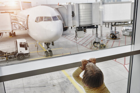 Little girl looking through window to airplane on the apron - RORF01058