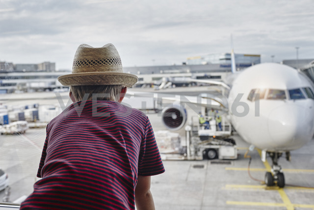 Boy wearing straw hat looking through window to airplane on the apron - RORF01061