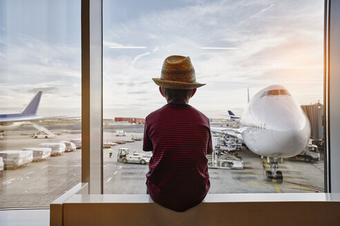 Boy wearing straw hat looking through window to airplane on the apron - RORF01064