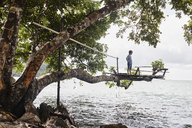 Thailand, Railay, Rai Leh East Beach, boy on tree house above the sea - RORF01070