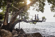 Thailand, Railay, Rai Leh East Beach, boy and little girl on tree house above the sea - RORF01073
