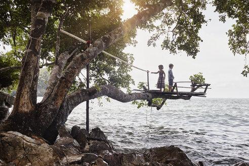 Thailand, Railay, Rai Leh East Beach, boy and little girl on tree house above the sea - RORF01073