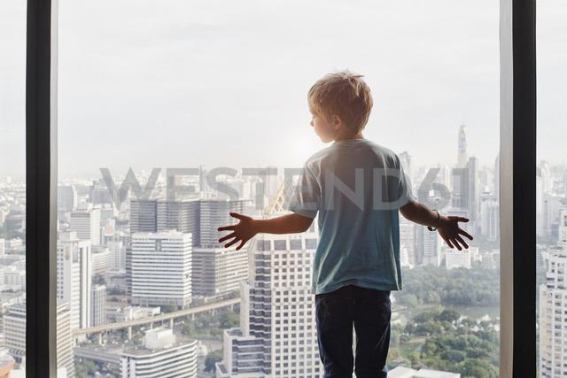 Thailand, Bangkok, boy looking through window at cityscape - RORF01082