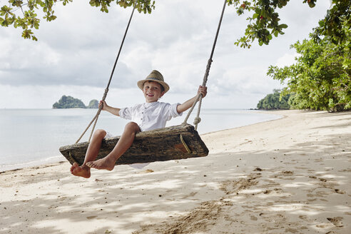 Thailand, Ko Yao Noi, happy boy on a swing on the beach - RORF01085