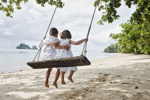 Thailand, Ko Yao Noi, boy and little girl on a swing on the beach - RORF01088