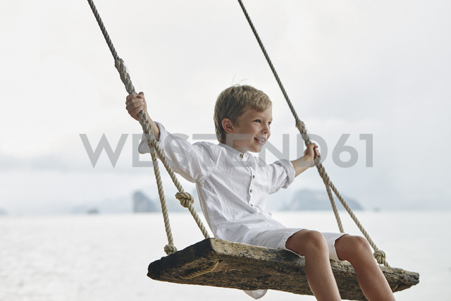 Thailand, Ko Yao Noi, happy boy on a swing on the beach - RORF01091