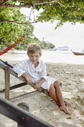 Thailand, Phi Phi Islands, Ko Phi Phi, portrait of boy sitting on deck chair on the beach - RORF01097