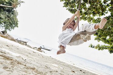 Thailand, Phi Phi Islands, Ko Phi Phi, happy little girl on a rope swing on the beach - RORF01103