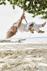 Thailand, Phi Phi Islands, Ko Phi Phi, happy little girl on a rope swing on the beach - RORF01106
