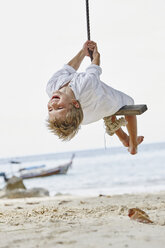 Thailand, Phi Phi Islands, Ko Phi Phi, happy boy on a rope swing on the beach - RORF01112