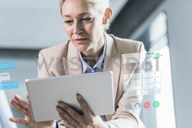 Businesswoman sitting in office, using digital tablet - UUF12531