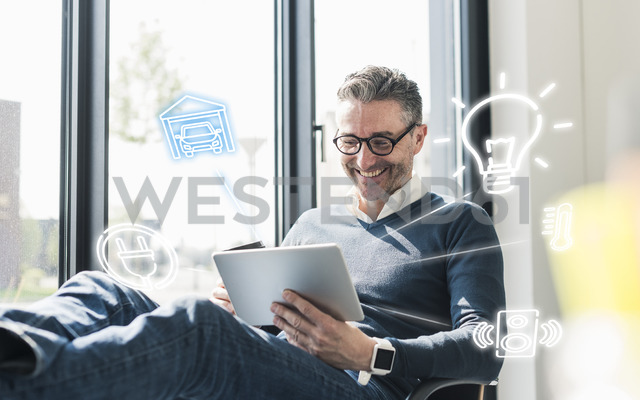 Man sitting in office, using digital tablet to remote-control his smart home - UUF12534