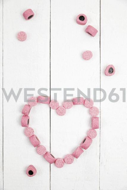 British licorice, heart on wooden background - GWF05404