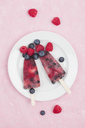 Fruit ice lollies with fresh raspberries and blueberries on plate - GWF05410