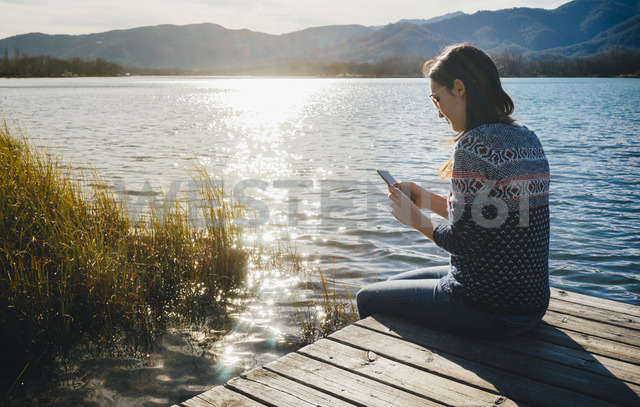 Woman sitting on a wooden platform at a lake at sunset, using smartphone - GEMF01856