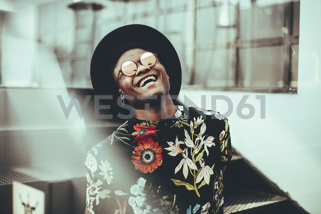 Portrait of laughing man wearing hat, sunglasses and black t-shirt with floral design - OCAF00058