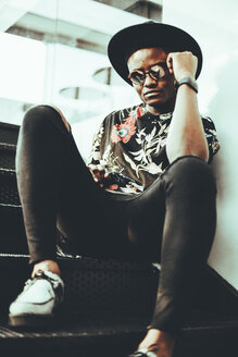 Portrait of fashionable man wearing hat, sunglasses and black t-shirt with floral design siitng on stairs - OCAF00061