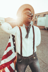 Portrait of laughing young man with American flag at backlight - OCAF00067