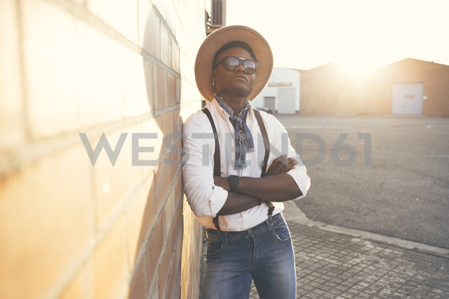 Portrait of cool young man wearing hat and sunglasses leaning against wall - OCAF00070