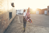 Back view of young man running with American flag at backlight - OCAF00073