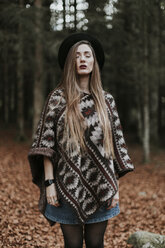 Portrait of young woman wearing hat and poncho standing in autumnal forest - OCAF00076