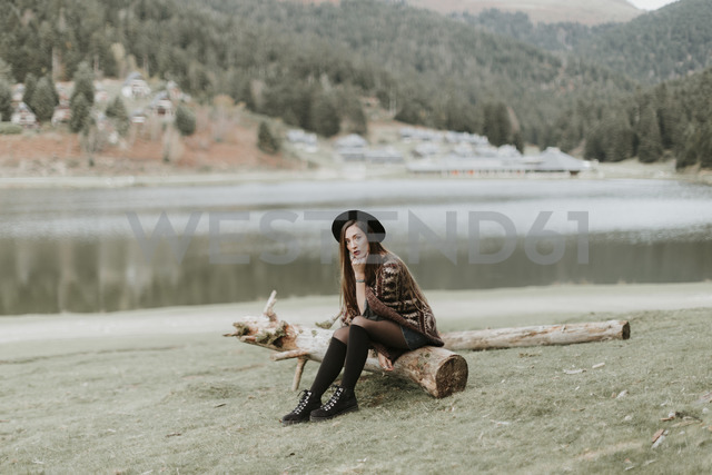 Fashionable young woman wearing hat and poncho sitting on log on a meadow - OCAF00079