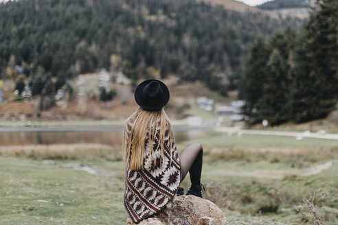 Back view of fashionable young woman wearing hat and poncho sitting on a rock - OCAF00082