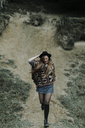 Fashionable young woman wearing hat and poncho running downhill - OCAF00085