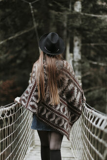 Back view of fashionable young woman wearing hat and poncho walking on suspension bridge - OCAF00088