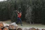 Young woman balancing on logs - OCAF00091