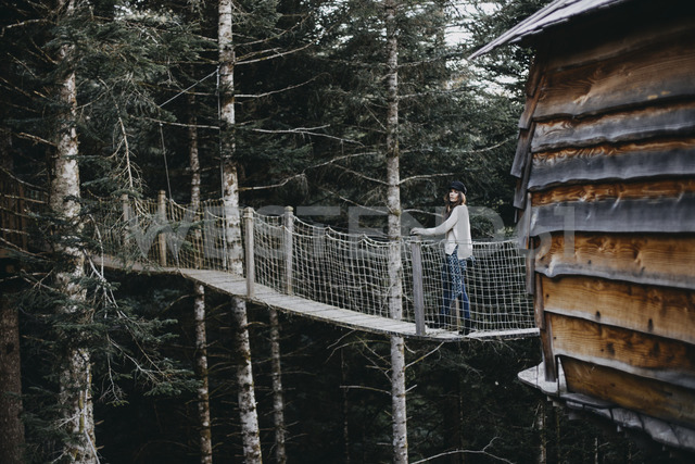 Young woman on a suspension bridge at tree house in forest - OCAF00095
