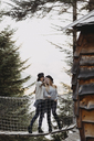 Two young women on a suspension bridge at tree house in forest taking a selfie - OCAF00098