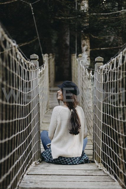 Smiling young woman sitting on a suspension bridge - OCAF00104