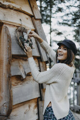 Happy young woman decorating wooden house with Christmas decoration - OCAF00107