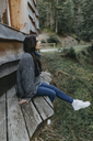 Young woman sitting at a wooden house in the nature - OCAF00110
