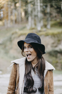 Portrait of happy young woman wearing flappy hat in the nature - OCAF00116