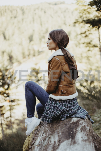Young woman sitting on a log in the nature - OCAF00119