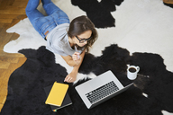 Young woman at home lying on the floor using laptop - BSZF00145