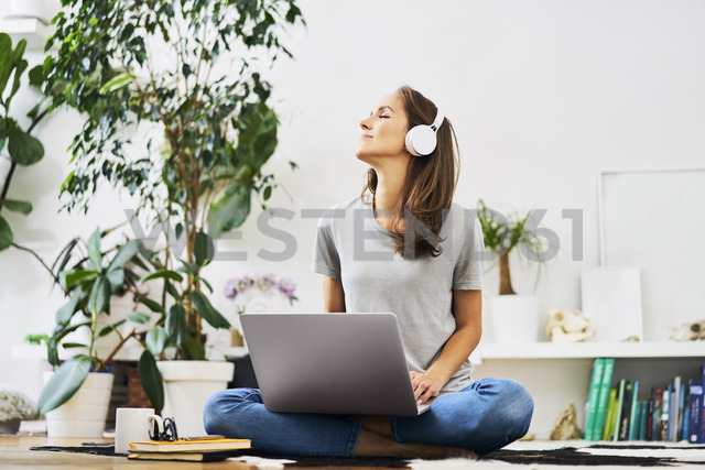Relaxed young woman at home sitting on the floor using laptop and listening to music - BSZF00151