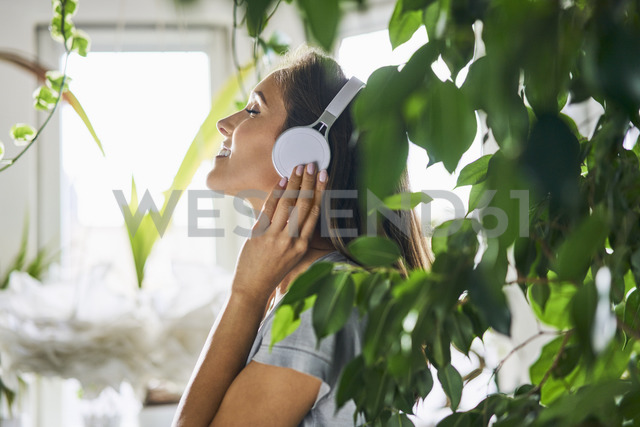 Smiling young woman with headphones listening to music at indoor plant - BSZF00157