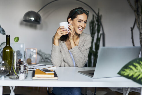 Happy young woman at home with laptop on desk - BSZF00166