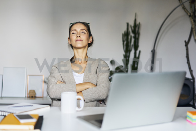 Young woman at home with laptop on desk having a break - BSZF00169