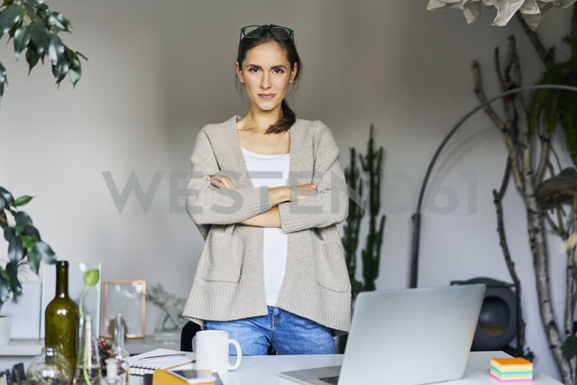 Confident young woman standing at desk with laptop - BSZF00172