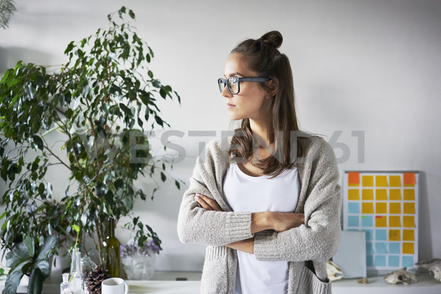 Confident young woman standing in office looking sideways - BSZF00178